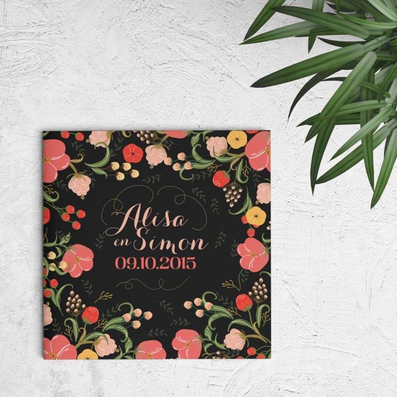 Trouwkaart Bloemen kent een veelvoud aan mooie, gedetailleerde, kleurrijke bloemen. De zwarte achtergrond is origineel en verrassend en zorgt voor contrast. Afbeelding toont voorkant van trouwkaartje.