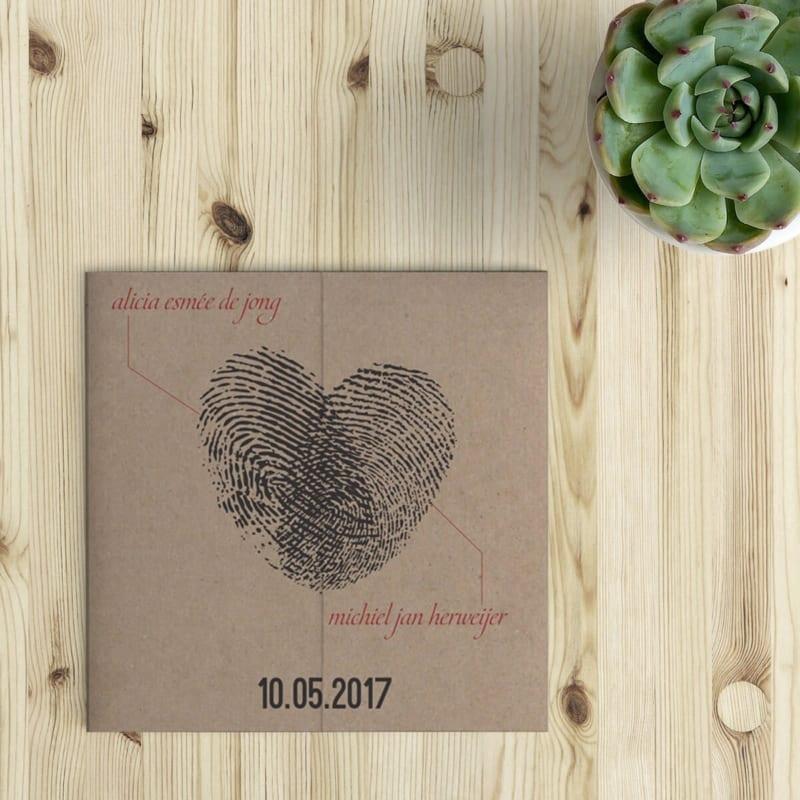Twee vingerafdrukken die samen een hart vormen. Trouwkaartje Vingerafdrukken (drieluik) wordt standaard op kraftpapier gedrukt. Voorkant van het trouwkaartje op houten ondergrond.