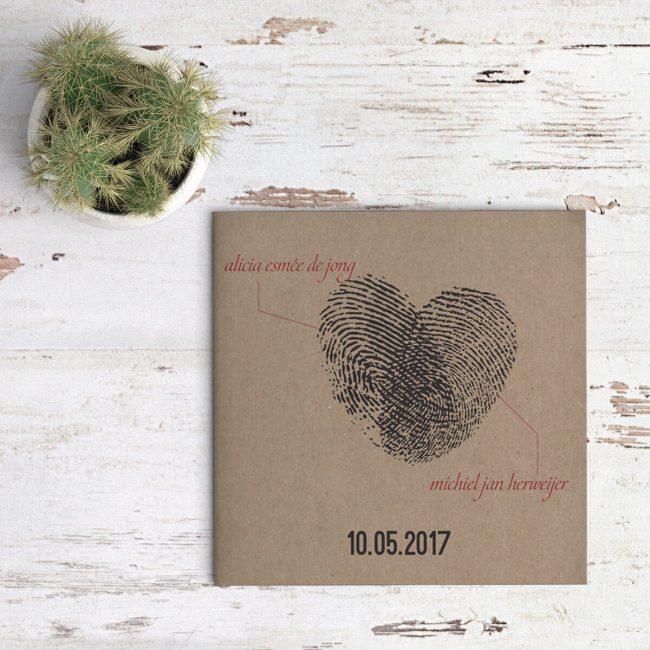 Trouwkaart Vingerafdrukken wordt standaard op kraftpapier gedrukt. Twee vingerafdrukken, in inkt, die samen een hart vormen, op de voorkant, met beide namen. Afbeelding toont voorkant van trouwkaart.