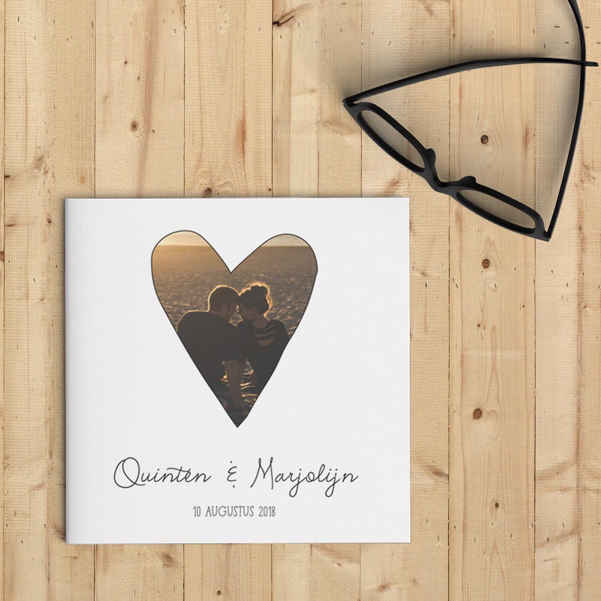 Trouwkaart Foto Hart gebruikt een foto in de vorm van een getekend hart op voorkant, met mooie lettertypes en een programma-tijdlijn met leuke icoontjes. Voorkant van trouwkaartje.
