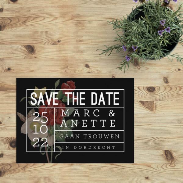 Bij Save the date kaart Tekst op Bloemen wordt er gespeeld met een zwarte achtergrond, een prachtig boeket daar bovenop, en daar weer bovenop een rechthoekig frame met witte lijnen en witte tekst.