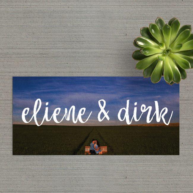 Bam! Trouwkaartje Foto draait er niet om heen: jullie namen staan in koeienletters, in het wit, bovenop een langwerpige foto die de gehele voorkant inneemt.