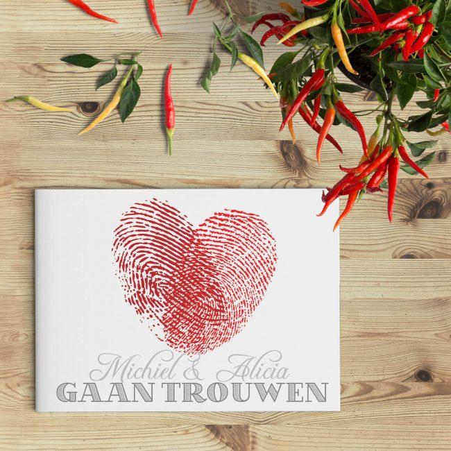 Modern trouwkaartje met hart gevormd door twee vingerafdrukken. Rood en grijs van kleur.