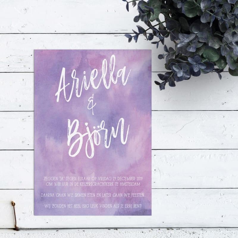 Eenvoudige trouwkaart met een achtergrond volledig in waterverf in paarse tinten. Een bijzonder sierlijk lettertype voor jullie namen, in grote letters.
