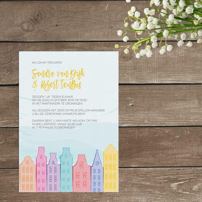 Trouwkaart Hollandse Huisjes, een fris, modern en kleurrijk ontwerp. Een rij met typische, Hollandse herenhuisjes in allerlei vrolijke kleuren. Grafische trouwkaarten met illustraties.