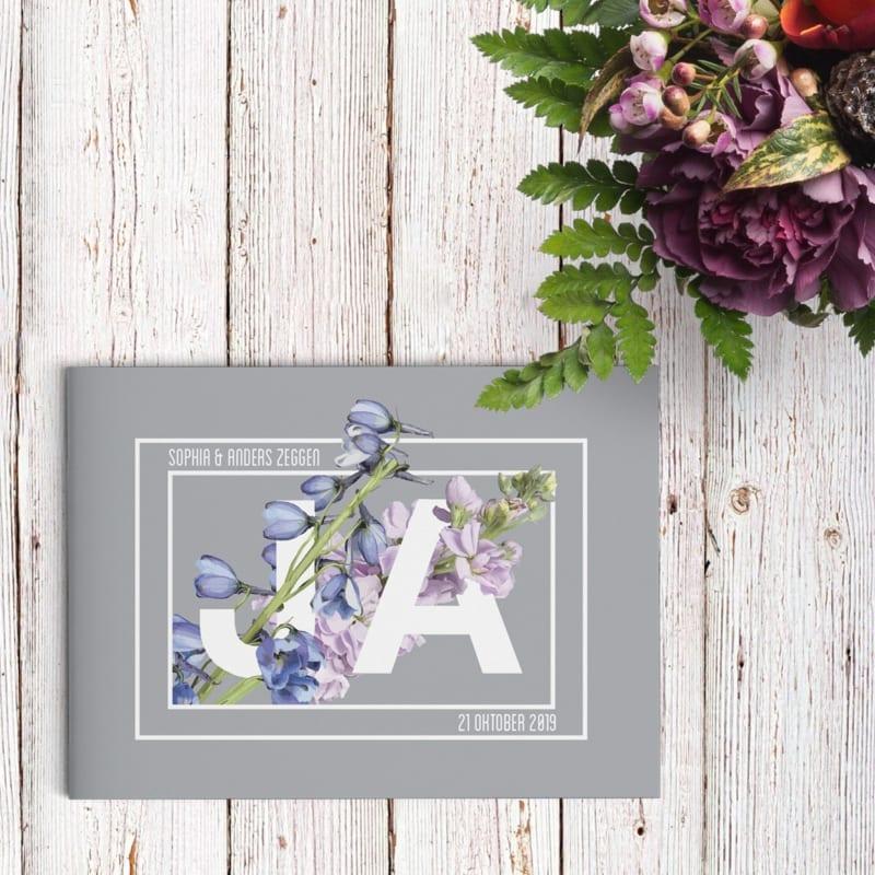 Trouwkaart Prachtig Bloemenspel bestaat uit het woord ja dat overweldigd wordt door bloemen.