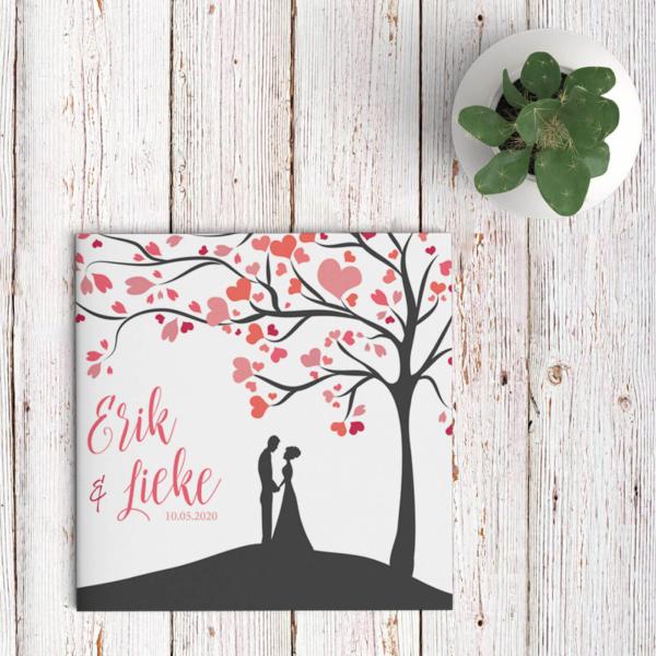 Trouwkaart Boom met Hartjes als Blaadjes is een romantisch & lieflijk ontwerp in zachte, roze tinten, een boom op een heuveltje met 2 verliefde mensen.