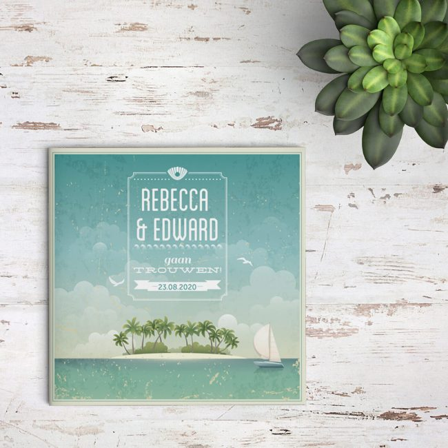 Trouwkaart Paradijs laat prachtig tafereel zien van tropisch eiland met zeilbootje en mooi trouw-monogram.