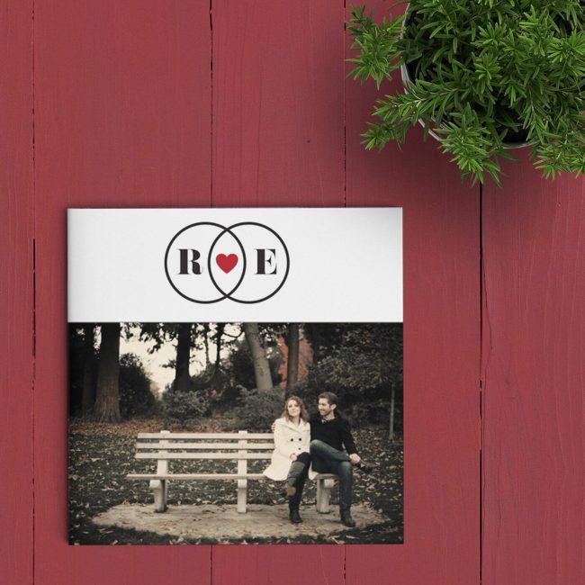 Op de voorkant van trouwkaart Ringen vormen twee overlappende ringen een trouwlogo, met jullie voorletters en een hartje. Een duidelijke boodschap: liefde.