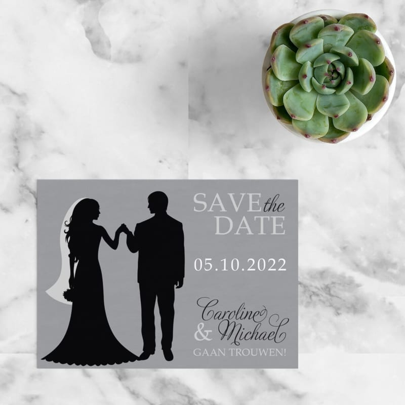 Save the date kaart Silhouet is abstract qua ontwerpstijl, met een silhouet van een bruidspaar, vlak voor de openingsdans, in het middelpunt. Kleuren zijn grijs, zwart en wit.