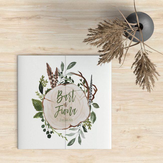 Trouwkaart Botanisch kondigt jullie bruiloft aan met de namen en trouwdatum geschreven op een dwarsdoorsnede van een boomstam.