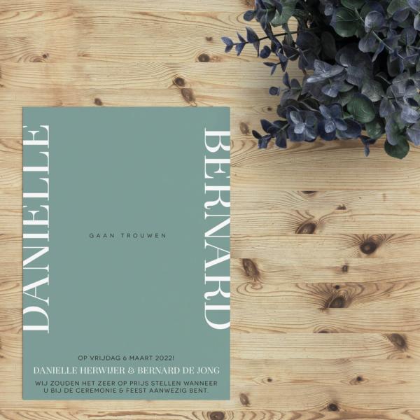 Trouwkaart Verticaal is een minimalistisch typografisch ontwerp, waarbij de namen van het bruidspaar verticaal tegen de zijkant zijn geplaatst.