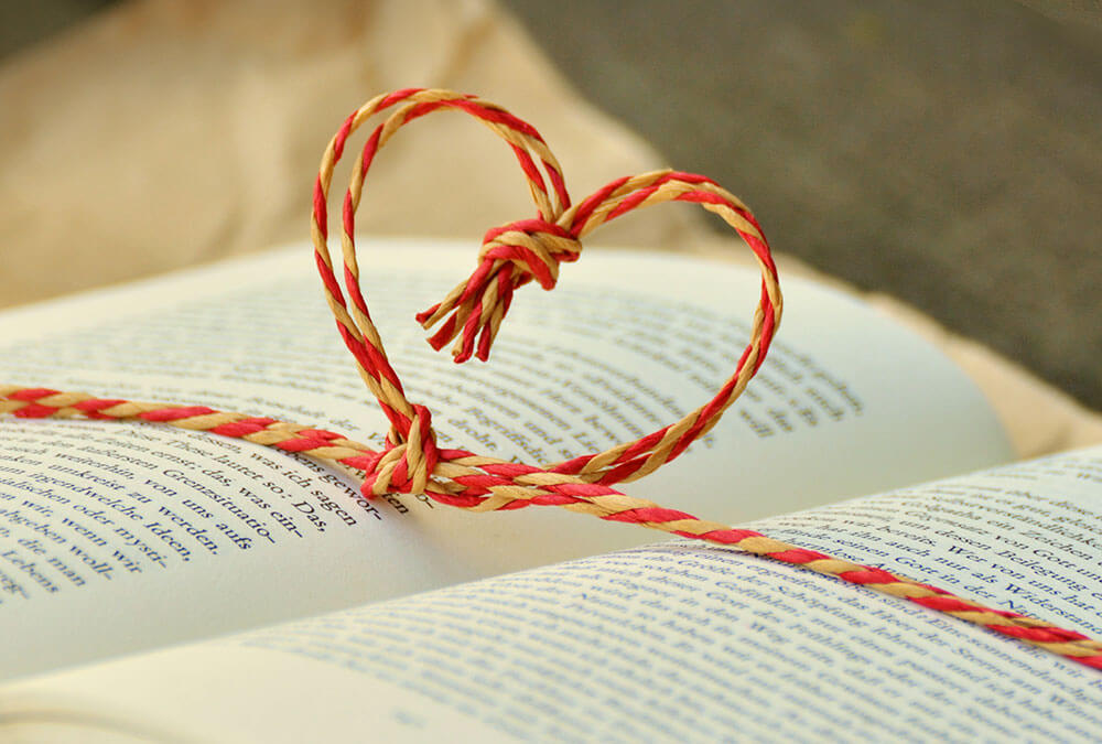 Hart op opengeslagen boek - Liefde staat voorop - Christelijke gedichten voor je trouwkaart