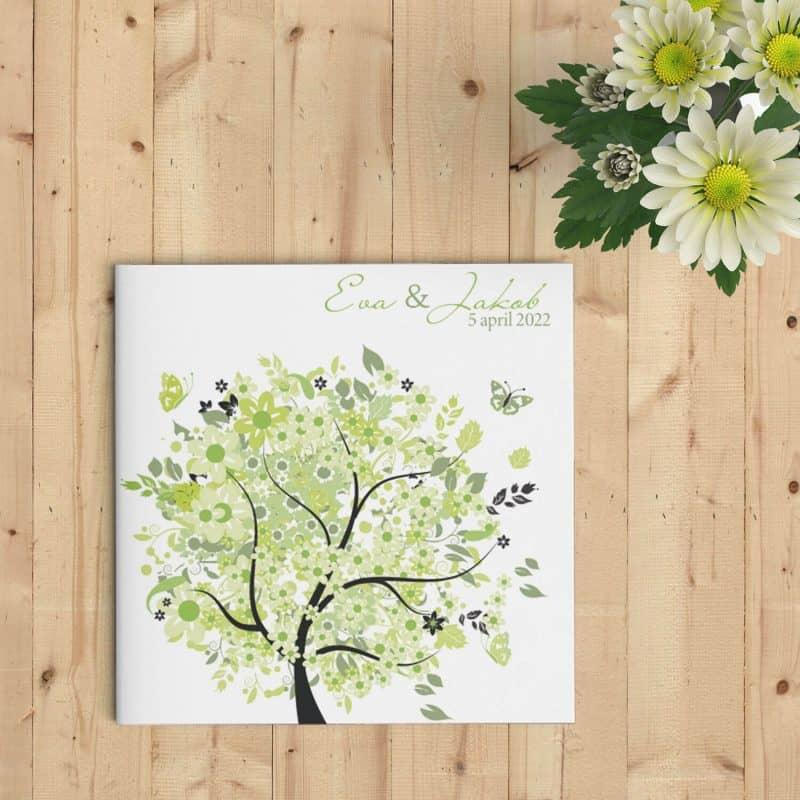 De vrolijke trouwkaart Boom van Geluk kan de juiste boodschap en gevoel doorgeven aan de mensen die jullie willen uitnodigen; gedetailleerde illustraties. Afbeelding toont voorkant van trouwkaart op houten ondergrond.