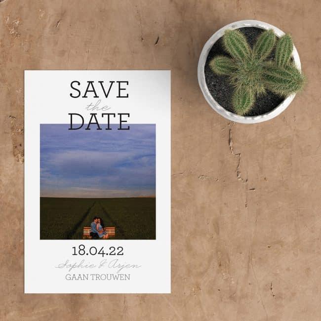 Save the date kaart Statement, daar zeg je iets mee. Een modern vormgegeven kaartje, met de woorden Save the date, in mooie eigentijdse lettertypes, die iets over de foto heen steken.
